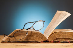 Book   and  glasses on wooden table. Book  and glasses on wooden table and blue background Stock Images