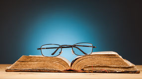 Book   and  glasses on wooden table. Book  and glasses on wooden table and blue background Royalty Free Stock Image