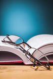 Book  and  glasses on wooden table. Book and glasses on wooden table and blue background Royalty Free Stock Photo