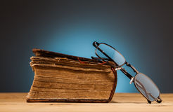 Book   and  glasses on wooden table Royalty Free Stock Photo