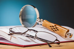 Book  and  glasses on wooden table. Book and glasses on wooden table and blue background Stock Photography