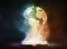 Book and globe. An open book glows brightly and reveals a globe of the world Royalty Free Stock Images