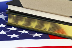 Book with gold pages on American flag Stock Photos