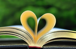 Book With Golden Pages on Table With Pages Forming Heart Stock Photo
