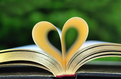 Book With Golden Pages on Table With Pages Forming Heart Stock Image