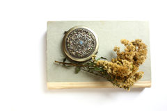 Book, goldenrod and pocket mirror Royalty Free Stock Photography