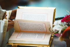 The Book of the Gospel is open for reading in the hands of the priest at the wedding.  Stock Photo