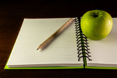 Book with green apple and pencil Stock Images