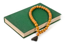 A book with a green cover and wooden rosary. Stock Photos