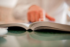 Book and hand. The businessman points a finger in the book on a light dim background Stock Photography
