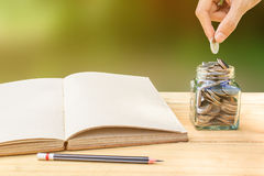 Book and hand putting coin into glass jar on wooden table with pencil. Stock Photos