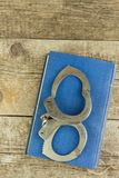 Book and handcuffs on a wooden table. The concept of punishment and justice. Punishment for a crime. Corruption and punishment. Royalty Free Stock Images