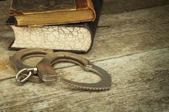 Book and handcuffs on a wooden table. The concept of punishment and justice. Punishment for a crime. Corruption and punishment. Stock Photography