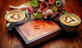 Book of Happiness. Newlyweds rings on a book with a cup of coffee and a bouquet of the bride royalty free stock image