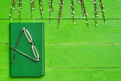 A book in a hard green cover on a green wooden background, glasses and willow branches. Top view. Copy space stock image