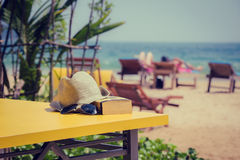 Book, hat and sunglasses, lying on a yellow table in a tropical Stock Images