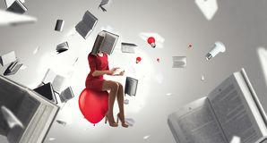 Book headed woman in red dress. Book headed businesswoman in a red dress sitting on balloon stock photos