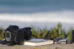 Book,headphones and photo camera. With the ocean in background, objects to take in a holiday weekend Stock Image