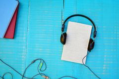 Audiobook concept. Book and headphones on wooden background Royalty Free Stock Photos
