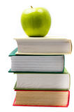 Book heap and green apple on top over white background Royalty Free Stock Image
