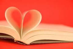 Book heart. A book with the pages forming a heart on a red background Stock Photo