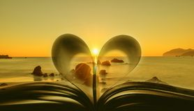 Book with heart-shaped leaves with the sea at sunrise in the background stock image