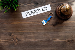 Book hotel. Word reserved near hotel service bell on dark wooden table background top view copyspace Stock Image