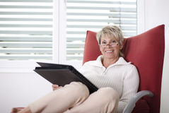 Book hour. Older woman holds on chair a photo album Stock Photography
