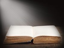 Book illuminated by bright beam of light Stock Photography