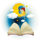 A book with an image of a fairy and a sleeping moon Royalty Free Stock Image