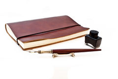Book ink and pen. A small book with a pen and ink in the background Royalty Free Stock Images