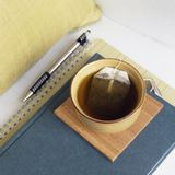 Cup of tea with book, journal and pen on chair with pillow. Relaxing, comfortable home interior elements details. royalty free stock photography