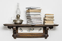 Book and kerosene lamp. On the old shelf Stock Photos