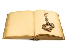 Book with key motif. Close-up of open old book with key motif, isolated on white stock image