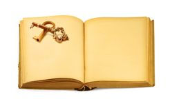 Book with key motif. Close-up of open old book with key motif, isolated on white stock photo