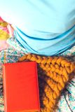 A book and a knitted hat. A book and a knitted cap on women`s legs. Winter hat made of thick yarn. An orange notebook lies on the bed Stock Images