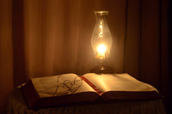 Book and lamp. Open book with oil lamp and reading glasses Royalty Free Stock Image