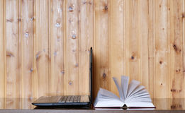 Book and Laptop on a wooden table. Wood background. E-learning. Education. Internet labrary Stock Image
