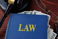 Book with Law, a gavel and cash. Royalty Free Stock Image