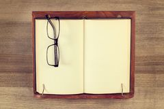 Book on a lectern. And pair of eye glasses stock image