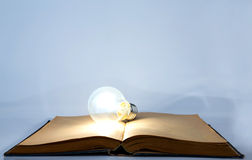 Book and light bulb Stock Photos