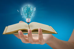 Book and light bulb on hand. On blue background Stock Images