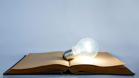 Book and light bulb. Light bulb on old book Royalty Free Stock Photography