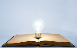 Book with light bulb. Light bulb on old book Royalty Free Stock Photography