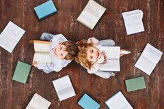 A book is like a garden, carried in the pocket. Children sitting near books, while looking at camera and smiling. They stock photos