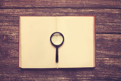 Book and loupe Royalty Free Stock Photos