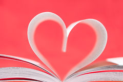 Book of love. Opened book with laid sheets of paper in form of heart on red background Stock Images