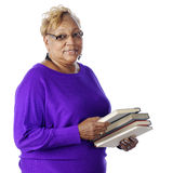 Book-Loving Senior. Closeup of a senior adult woman carrying the books she loves to read.  On a white background Royalty Free Stock Photos