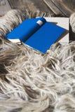Book lying on Fur carpet, close-up Stock Photo