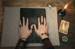 Book of magic. Future reading. Book of magic on fortune teller concept. Tarot cards on fortune teller desk table. Future reading. Woman witch reads a ancient Stock Photos